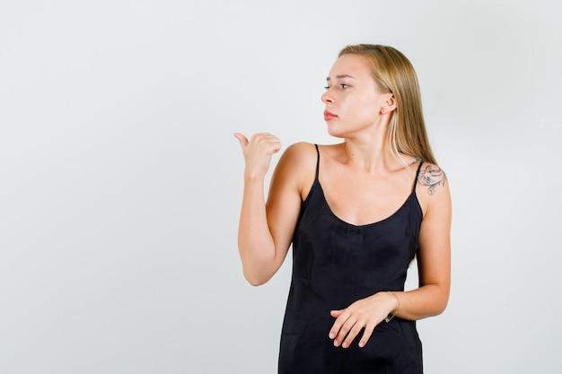 Mujer joven en camiseta negra apuntando hacia atrás con el pulgar y mirando serio