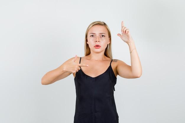 Mujer joven en camiseta negra apuntando con el dedo con gesto de pistola y mirando serio