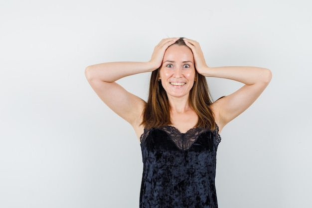 Mujer joven en camiseta negra cogidos de la mano en la cabeza y mirando dichoso