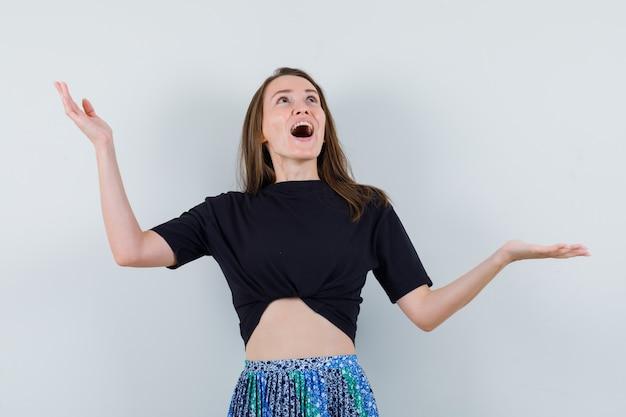 Mujer joven en camiseta negra y falda azul abriendo los brazos y mirando hacia arriba y mirando feliz