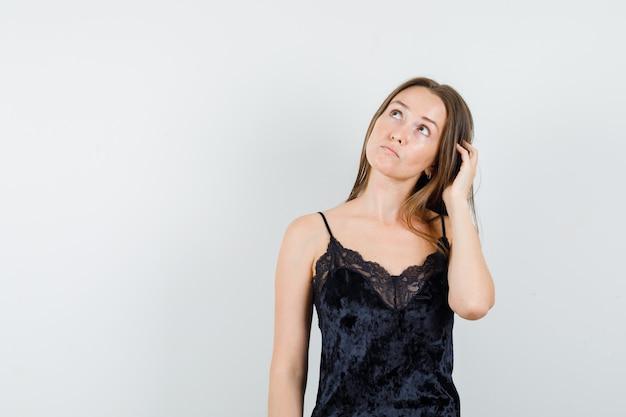 Mujer joven en camiseta negra mirando hacia arriba mientras se rasca la cabeza y mira pensativa
