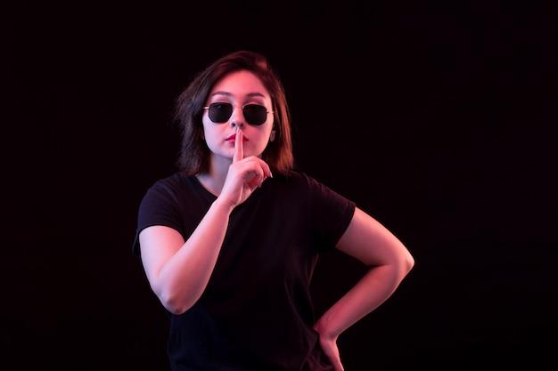 Mujer joven con camiseta negra pidiendo silencio