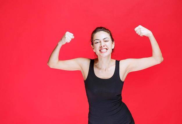 Mujer joven en camiseta negra de pie sobre la pared roja y demostrando los músculos de su brazo
