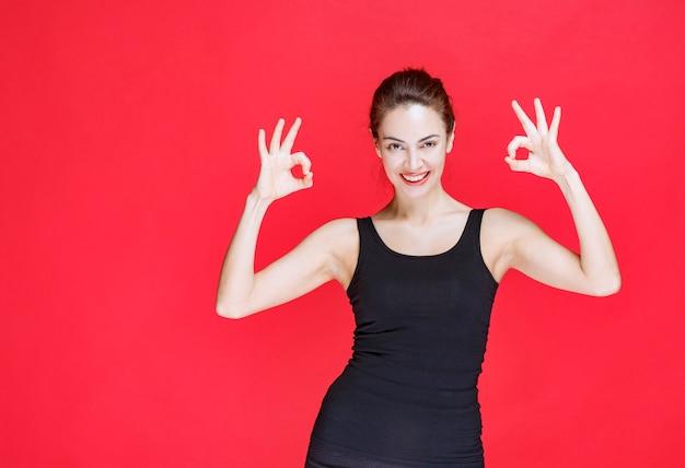 Mujer joven en camiseta negra de pie sobre la pared roja y mostrando el signo de ok