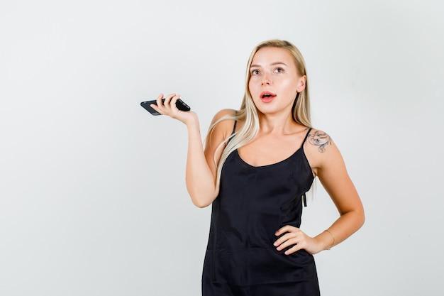 Mujer joven en camiseta negra posando mientras sostiene el teléfono inteligente y parece encantador