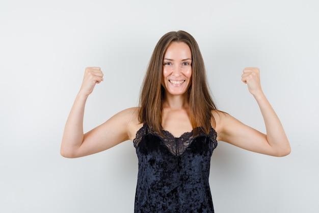 Mujer joven en camiseta negra que muestra el gesto del ganador y parece feliz