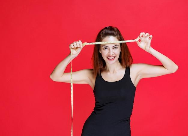 Mujer joven en camiseta negra sosteniendo una cinta métrica