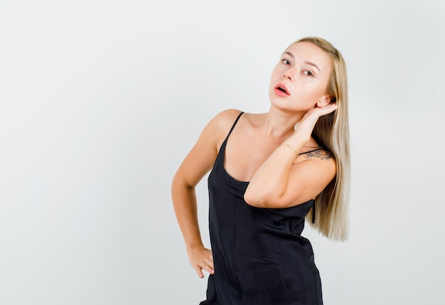 Mujer joven en camiseta negra tratando de escuchar algo confidencial y con aspecto serio