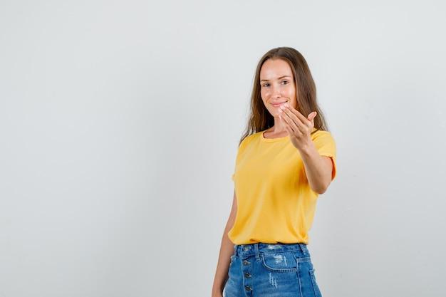 Mujer joven en camiseta, pantalones cortos sonriendo e invitando a venir