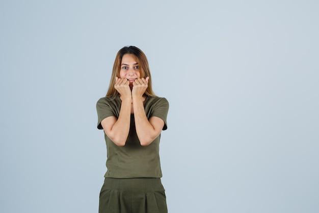 Mujer joven en camiseta, pantalones tomados de la mano cerca de la boca y mirando feliz, vista frontal.
