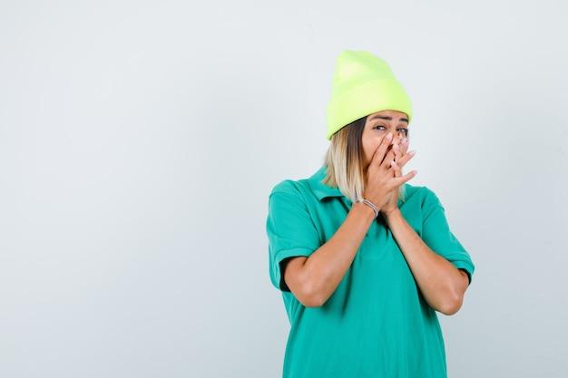 Mujer joven en camiseta de polo, gorro cubriendo la boca con las manos entrelazadas y mirando curioso, vista frontal.