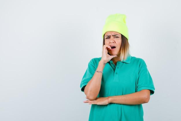 Mujer joven en camiseta de polo, gorro manteniendo la mano en la mejilla y mirando soñoliento, vista frontal.