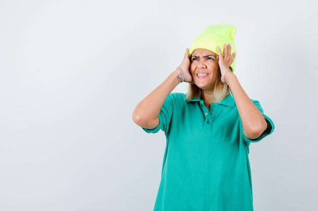 Mujer joven en camiseta de polo, gorro manteniendo las manos en la cabeza y mirando alegre, vista frontal.