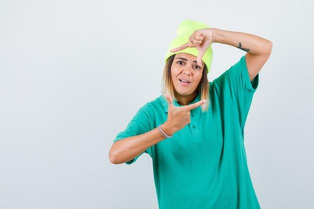 Mujer joven en camiseta de polo, gorro mostrando gesto de marco y mirando contento, vista frontal.