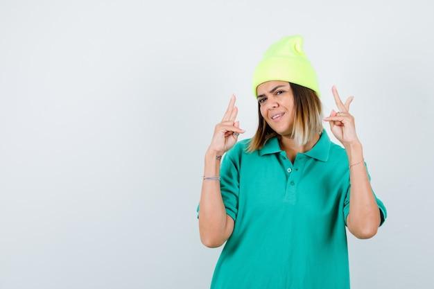 Mujer joven en camiseta de polo, gorro mostrando gesto de victoria y mirando alegre, vista frontal.
