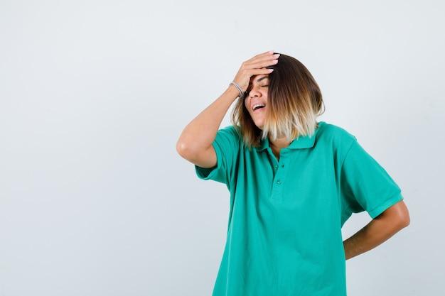 Mujer joven en camiseta de polo con la mano en la frente mientras mantiene la mano detrás de la espalda y se ve feliz, vista frontal.