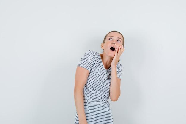 Mujer joven en camiseta de rayas mirando hacia arriba con la mano en la mejilla y mirando asombrado, vista frontal.