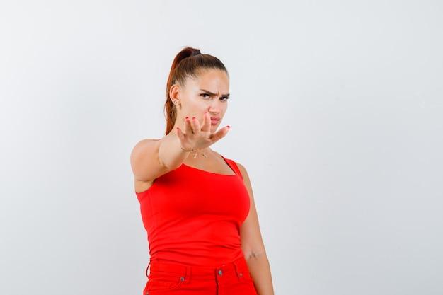 Mujer joven en camiseta roja, pantalones mostrando gesto de parada y mirando asustado, vista frontal.