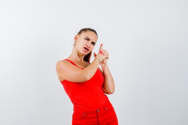 Mujer joven en camiseta roja, pantalones mostrando el signo de la mano de la pistola y mirando triste, vista frontal.