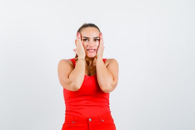 Mujer joven en camiseta roja, pantalones tomados de la mano en las mejillas y luciendo linda vista frontal.
