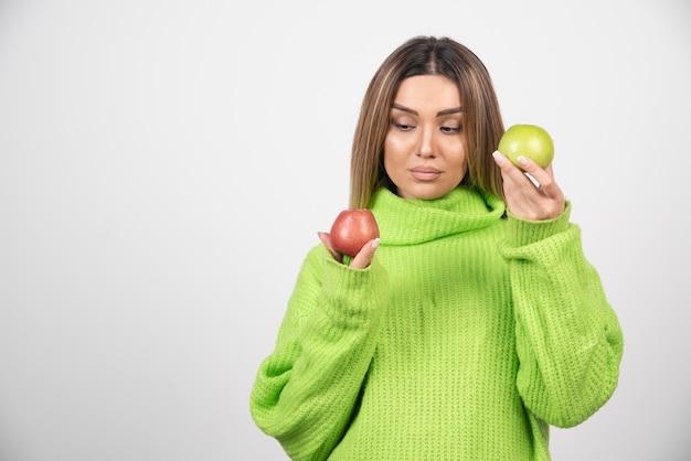 Mujer joven en camiseta verde sosteniendo dos manzanas arriba.