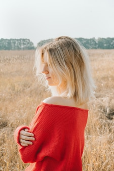 Mujer joven en un campo al atardecer. resplandor del sol.