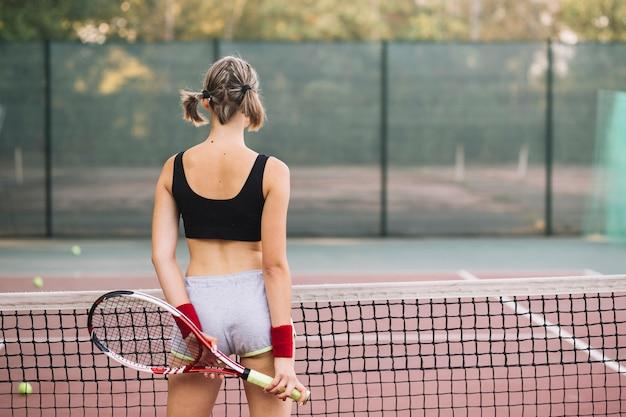 Mujer joven en el campo de tenis preparado para jugar