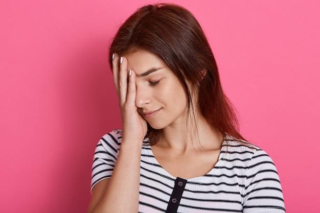 Mujer joven cansada cubre la cara con la palma, cierra los ojos, se siente agotada, usa una camiseta a rayas casual, posa aislada sobre una pared rosa, quiere dormir.