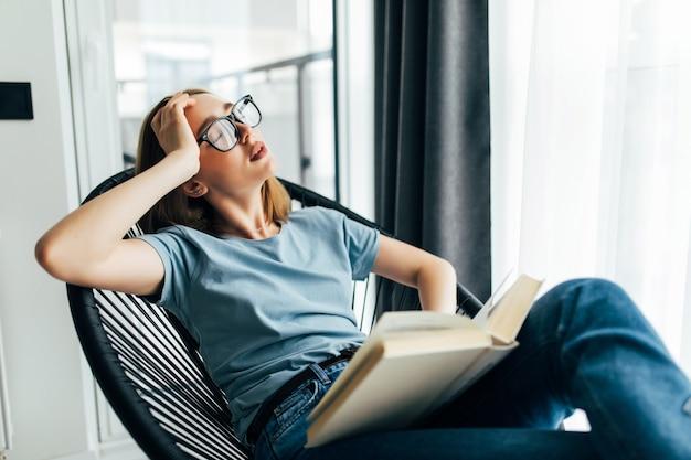 Mujer joven cansada con libro durmiendo en un sillón en casa