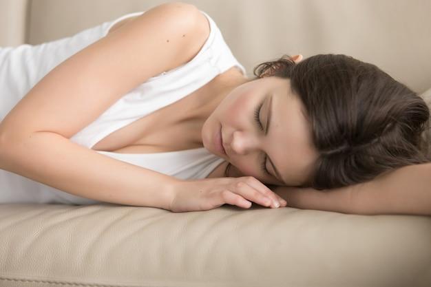 Mujer joven cansada que duerme en el sofá suave