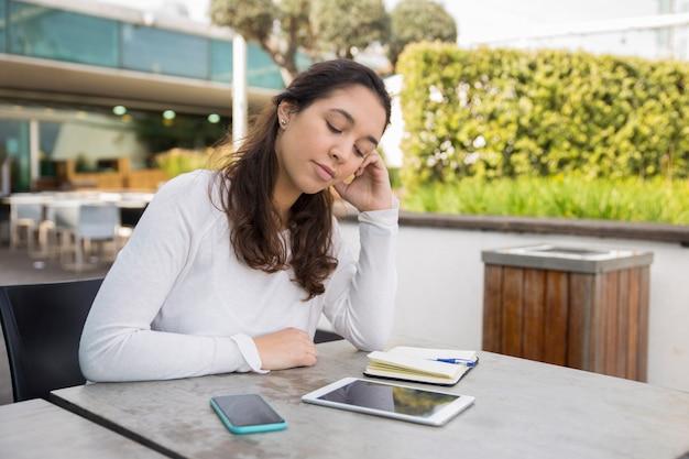Mujer joven cansada que se sienta en el café y que estudia o que trabaja