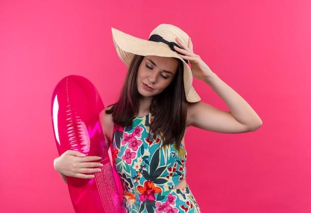 Mujer joven cansada con sombrero sosteniendo el anillo de natación y poniendo la mano sobre su cabeza en la pared rosa aislada