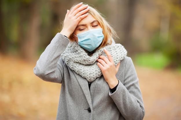 Mujer joven en una capa gris caminando en el parque de otoño con una máscara