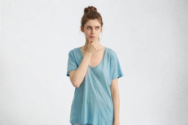 Mujer joven con cara ovalada, ojos azules atractivos con el pelo atado en un nudo vestida con una camisa suelta sosteniendo la mano en la barbilla mirando con expresión soñadora frunciendo el ceño pensando en algo