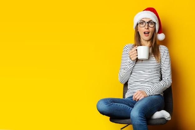 Mujer joven con cara de sorpresa en santa sombrero se sienta en una silla y sostiene una taza