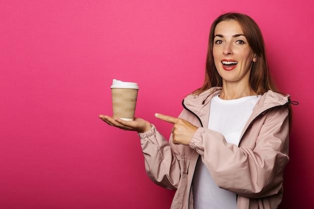 Mujer joven con cara de sorpresa sosteniendo una taza de papel con café