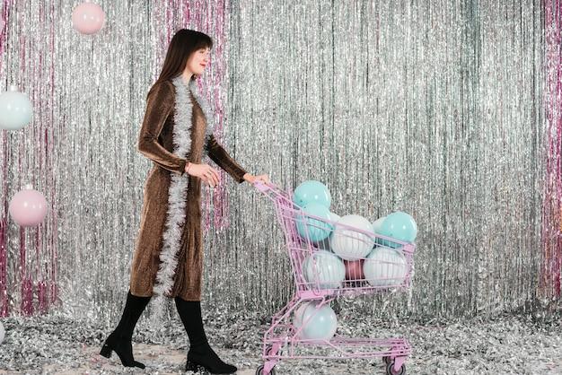 Mujer joven con carrito de la compra con lámparas decorativas cerca de oropel
