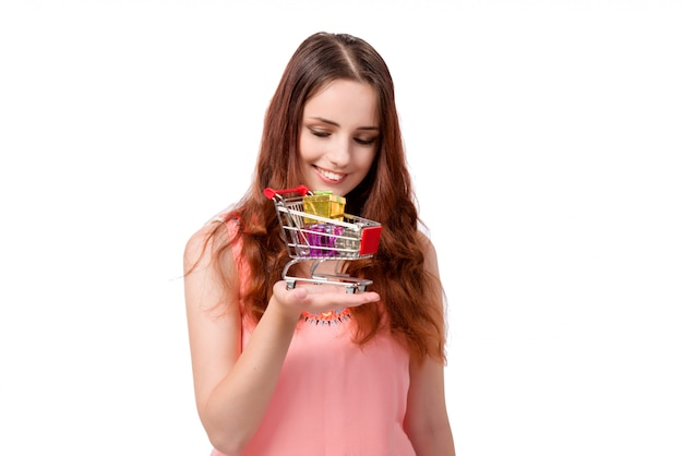 Mujer joven con carrito de compras aislado en blanco
