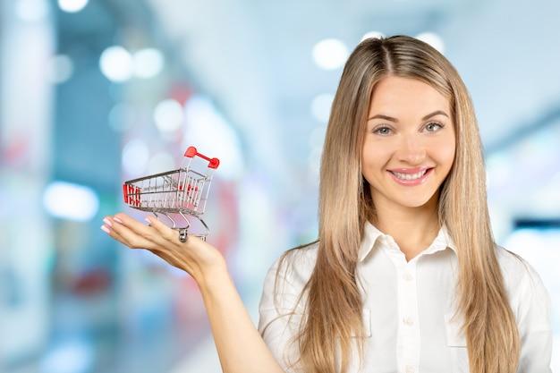 Mujer joven con un carrito de compras en miniatura. comercio electrónico y concepto de negocio