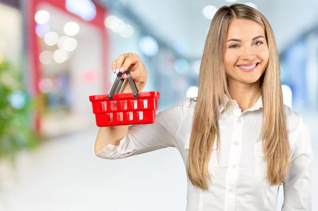 Mujer joven con un carrito de compras en miniatura