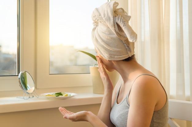 Mujer joven en casa cerca de la ventana mirando en el espejo