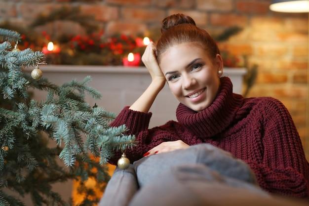 Mujer joven en casa con decoración navideña