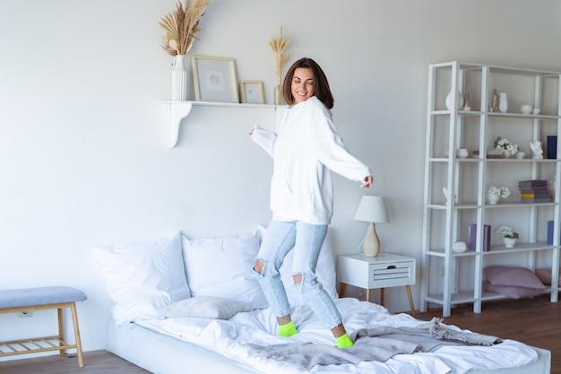 Mujer joven en casa en el dormitorio con una sudadera con capucha blanca cálida, divirtiéndose, saltando en la cama, bailando