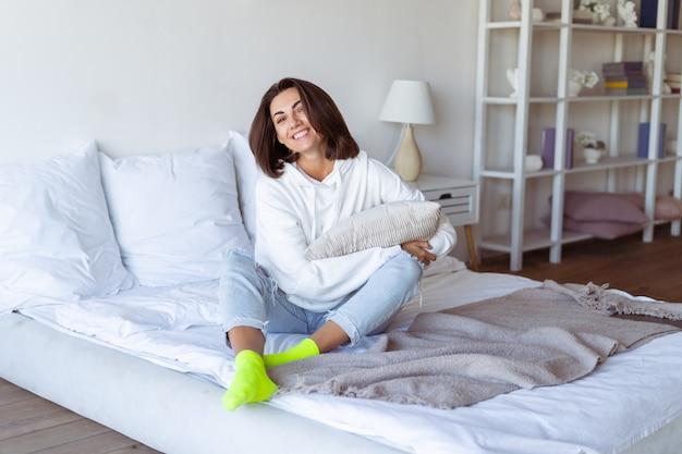 Mujer joven en casa en el dormitorio con una sudadera con capucha blanca cálida, feliz, en la cama con calcetines de neón verde brillante