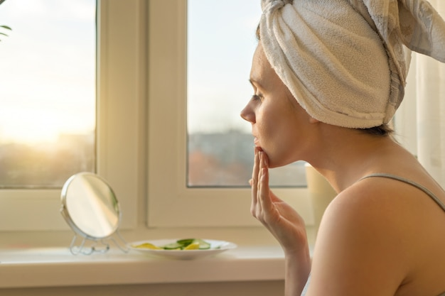 Mujer joven en casa mirando en el espejo