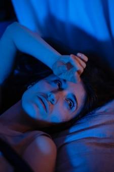 Mujer joven en casa con misteriosas luces de dormitorio