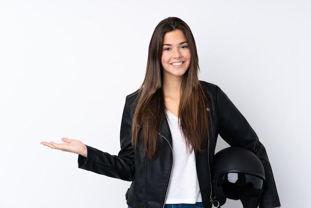 Mujer joven con un casco de moto sobre pared blanca aislada sosteniendo copyspace imaginario en la palma