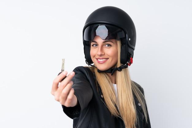 Mujer joven con un casco de moto sobre pared blanca aislada