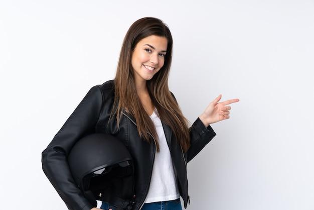 Mujer joven con un casco de motocicleta sobre la pared blanca aislada que señala el dedo hacia un lado