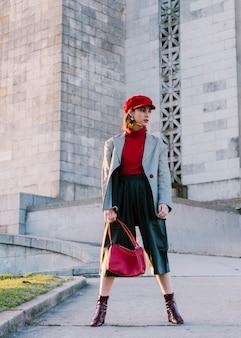 Mujer joven en el casquillo rojo que sostiene el bolso que se coloca delante del edificio